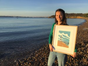 Noémie Courant stands on a beach with one of her linocuts depicting a lighthouse